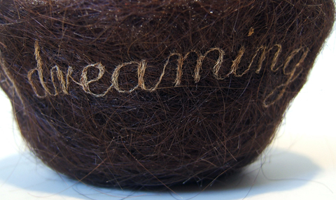 "Kate Kretz - ""Decades of Dreaming of You..."", 2012, hair embroidery on mother's hair from gestation period, threads from unraveled pillowcase, 3 x 5 x 5"". Embroidered text reads, ""decades of dreaming of you..."""