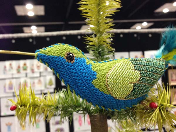 A variety of stitches, threads and ephemera (wire, feathers) come together to make this stunning needlepoint hummingbird. Painted canvas design by Labors of Love design company.