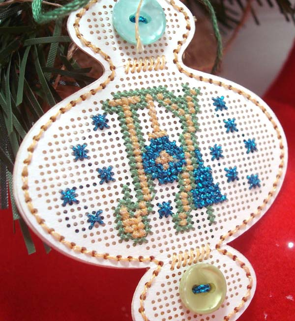 Kreinik metallic threads in cross stitch on perforated paper ornament shape.