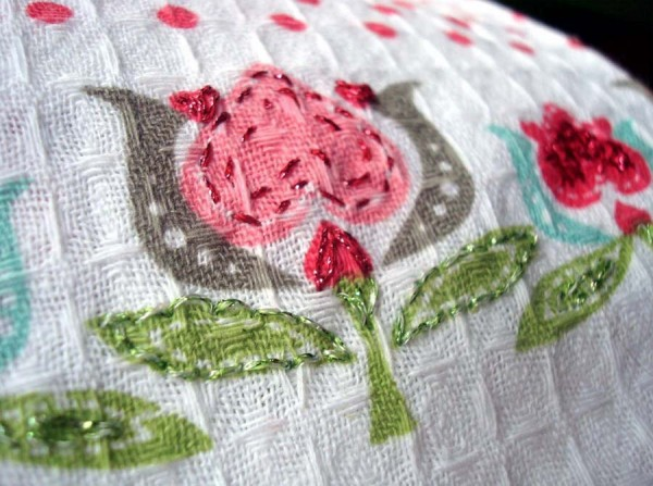 Sweet and soft metallic threads worked in basic backstitches add elegance to this dollar-store tea towel.