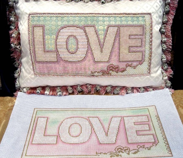 This design is a simple word painted on needlepoint canvas, but it is brought to textile life through a variety of threads and stitches. Design by Lani Silver of Lani's <a class=