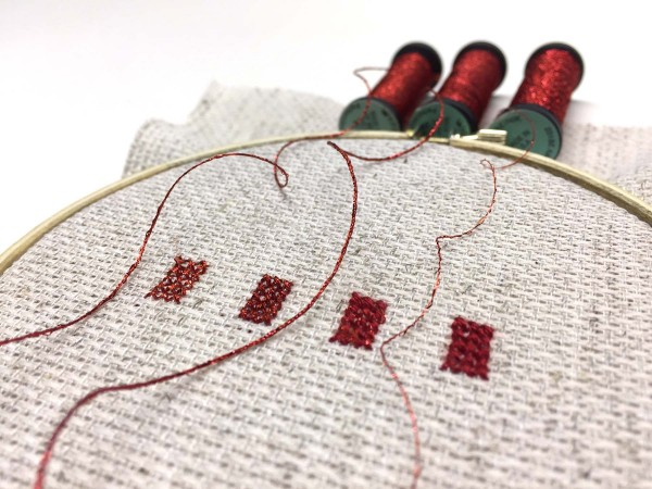Cross stitches of Kreinik Braids and Blending Filament to show the various degrees of metallic effects you can create.