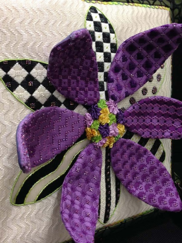 "Pretty in purple, this daisy stands out for...well, standing out. It's called ""3-D Daisy"" and is from the design company Sew Much Fun. Can you spot the Kreinik metallics?"