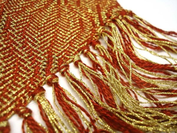 This is a classic pattern from DJE Handwoven's line, but remade using metallic threads. The look is so elegant, while the drape is still soft. Here, Deb used Kreinik Fine #8 gold Braid and an 8/2 Tencel for the rust color.