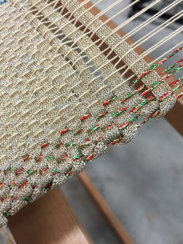 This swatch came from Doug Kreinik, who bought a rigid heddle loom last year. He now makes yarns in the Kreinik factory just for weaving (the gold shoelace yarn in the weft is an experiment). The red/gold/green metallic in the warp is one of Kreinik's most popular needlepoint colors.