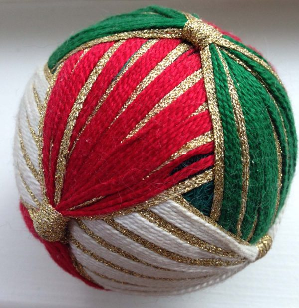 """This holiday themed wrapped ball comes from the Kreinik museum. It features silk threads and Kreinik 1/8"""" Ribbon."""