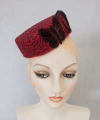 Red felt cocktail hat with hand embroidery.