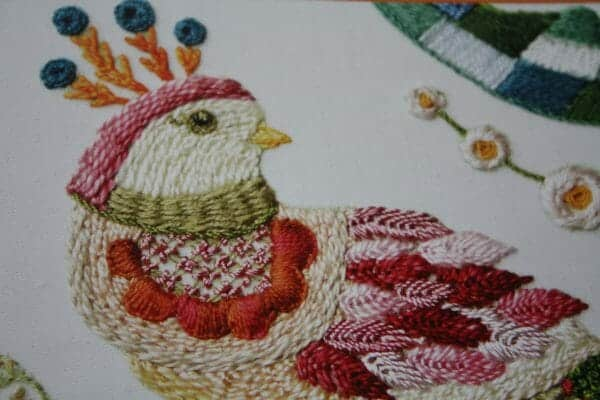 Crewel Embroidery: 7 enchanting designs inspired by fairy tales by Tatiana Popova - close up of one of the finished projects, a bird this time