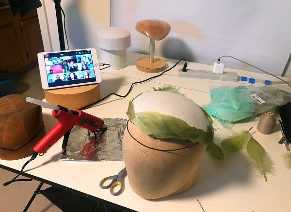 Messy worktable with iPad showing a Zoom meeting and an in-progress, feather-covered headpiece.